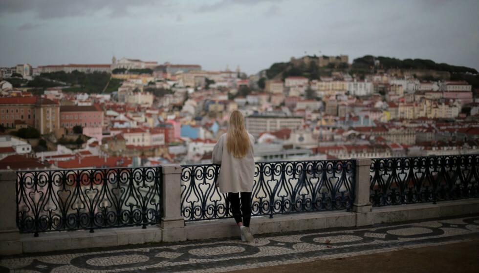 En kvinne ser utover Lisboa i Portugal. Landet har de siste ukene hatt blant verdens høyeste smitte- og dødstall, men nå stiger håpet om at det verste kan være over. Foto: Armando Franca / AP / NTB