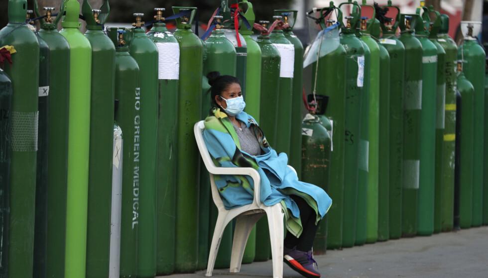 Mens flere hundre samfunnstopper har sneket i vaksinekøen i Peru, har vanlige borgere selv vært nødt til å skaffe oksygen til syke familiemedlemmer. Kvinnen på bildet var i kø for å få fylt opp en oksygenflaske i byen Callao i begynnelsen av februar. Foto: Martin Mejia / AP / NTB