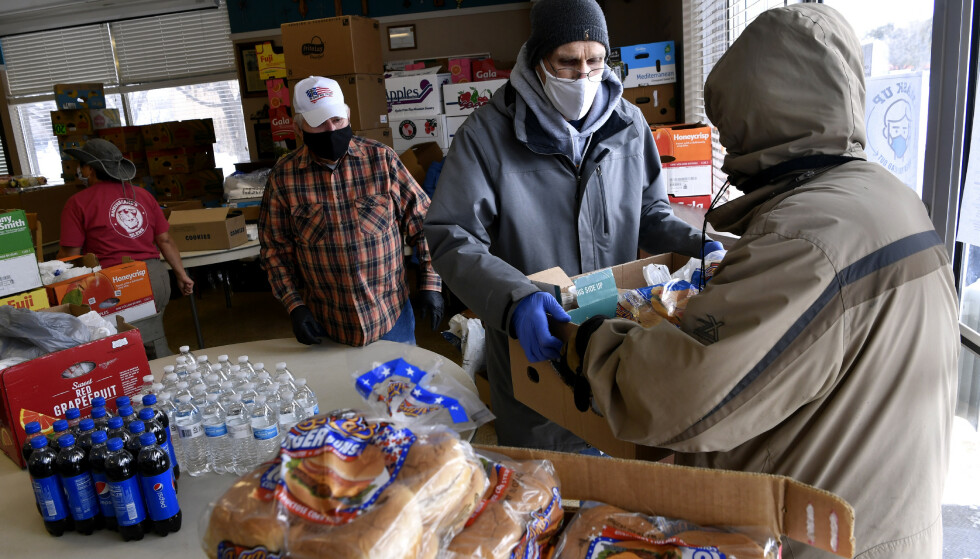 Bob Fink gir en eske med mat til en besøkende i City Light Community Ministries i Abilene i Texas. Bildet er tatt onsdag. Kjøkkenet der deler ut mat til folk med behov og har også en varmestue for dem som mistet strømmen. Foto: Ronald W. Erdrich / AP / NTB