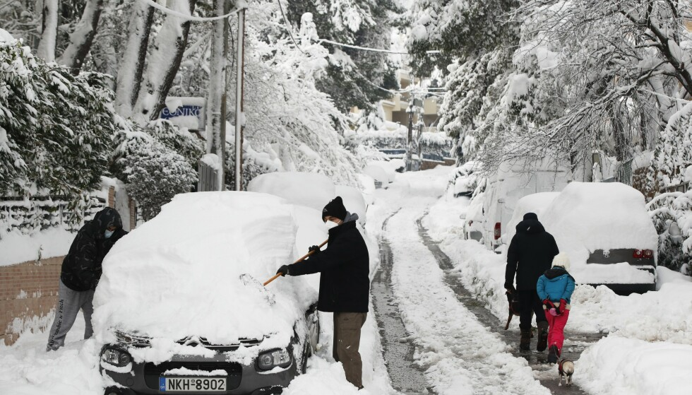 En mann og en gutt i ferd med å fjerne snø fra en bil i en forstad til Aten onsdag i forrige uke. Foto: Thanassis Stavrakis / AP / NTB