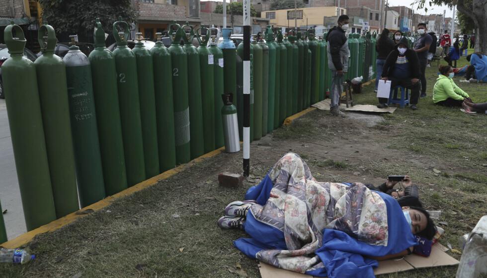 I Peru har folk sovet ute i kø for å skaffe seg oksygenbeholdere til syke pårørende. Foto: AP-NTB