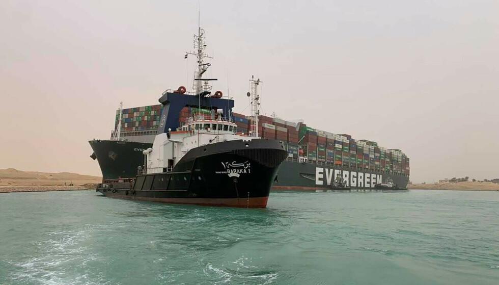 Fartøyet hadde torsdag morgen sittet fast i Suezkanalen i omtrent et døgn. Arbeidet med å få et av verdens største konteinerskip av grunn i Suezkanalen pågår fortsatt, men det kan ta flere dager før trafikken går som normalt igjen. Foto: AP / NTB