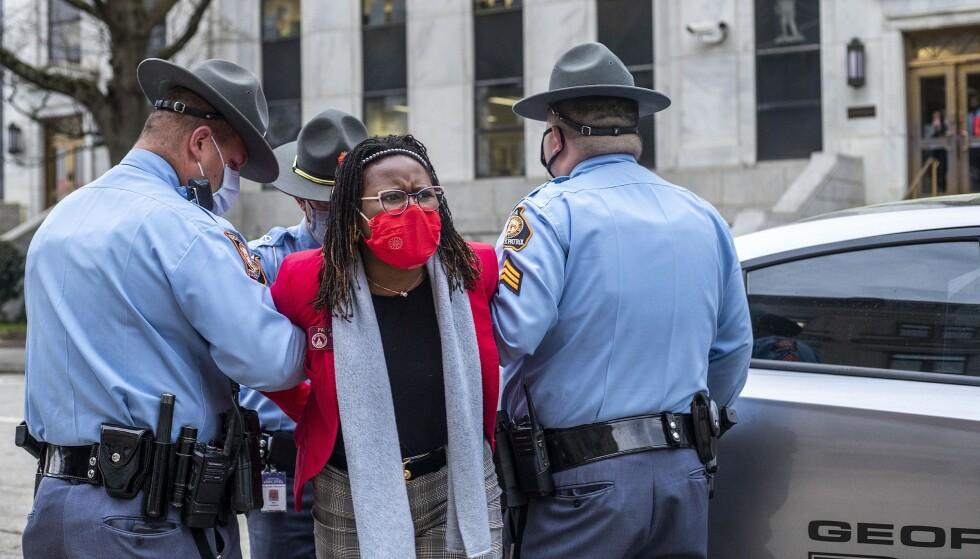 Delstatsrepresentanten Park Cannon, som er demokrat, pågripes av politiet etter at hun forsøkte å komme inn på kontoret til Georgia-guvernør Brian Kemp. Hun ville overvære Kemps signering av en valglov som kritikerne mener vil begrense valgdeltakelsen for svarte velgere. Foto: Alyssa Pointer / Atlanta Journal-Constitution via AP / NTB