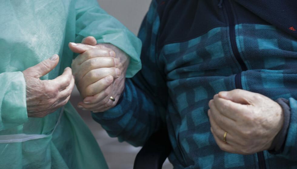 Palmiro Tami (82) trilles av sykehjemsdirektør Maria Giulia Madaschi. Ved siden av, i grønt beskyttelsesutstyr, går hans kone Franca Persico. Foto: Luca Bruno / AP / NTB