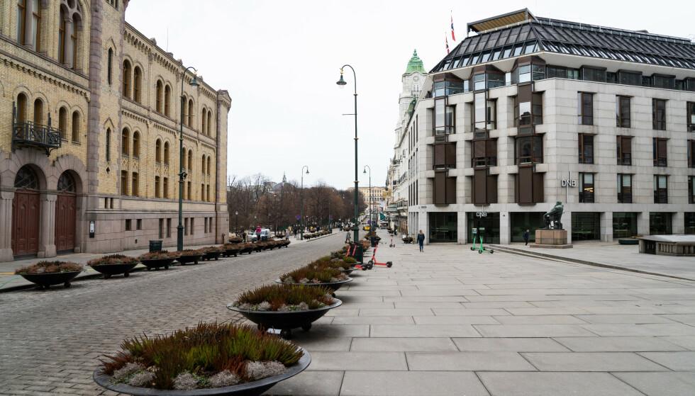 Et fåtall mennesker å se i Karl Johans gate i Oslo. Corona-pandemien har ført til en nedstengt hovedstad. Foto: Erik Johansen / NTB