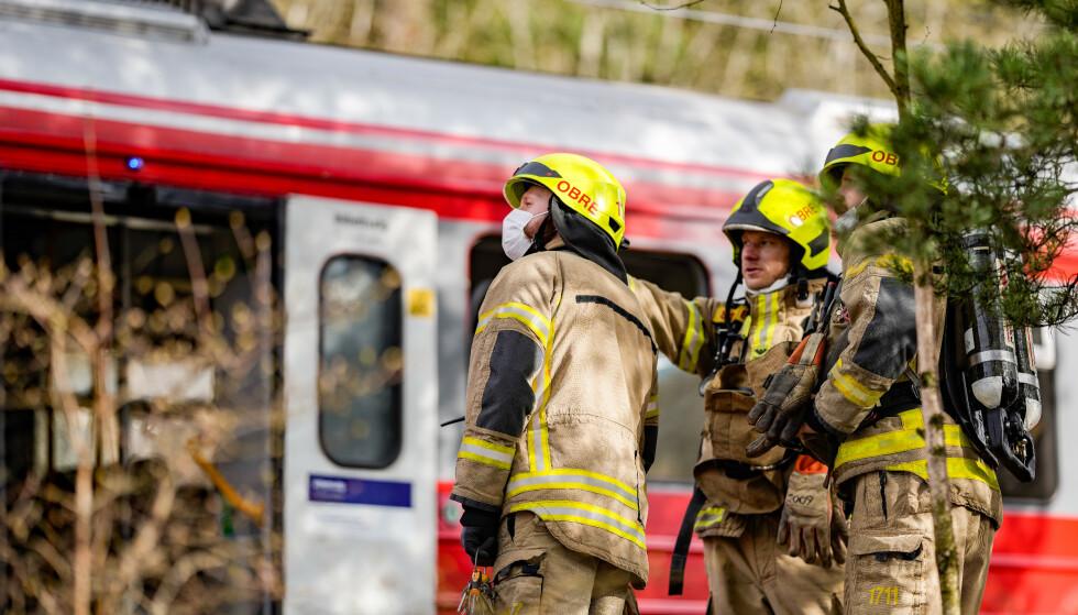 Mannskaper fra Oslo brann- og redningsetat på stedet der en kjøreledning har falt ned på et tog ved Rosenholm stasjon sør i Oslo. Foto: Fredrik Hagen / NTB