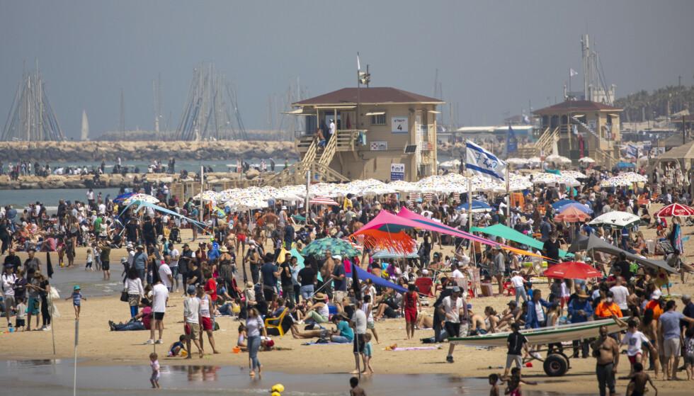 Livet begynner å vende tilbake til normaltilværelse i Israel. Bildet er fra Tel Aviv torsdag der folk strømmet til stranden på landets uavhengighetsdag. Foto: Ariel Schalit / AP / NTB