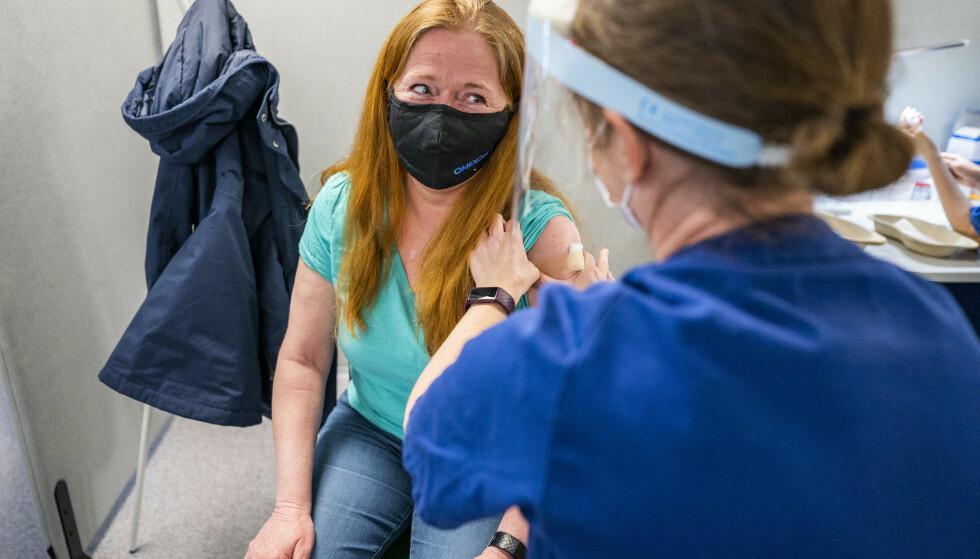 Hilde Arnesen (52) ser takknemlig på sykepleier Åshild Skårland som setter på plaster etter sprøytestikket på vaksinesenteret i Bjerke bydel. Arnesen fikk sin vaksinedose fredag, og om seks uker får hun andre dose og vil med det være fullvaksinert. Foto: Håkon Mosvold Larsen / NTB