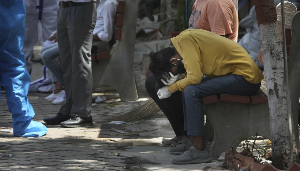 India går gjennom sin andre smittebølge. Her en slektning til et av covid-19s ofre utenfor et krematorium i New Delhi. Foto: Manish Swarup / AP / NTB