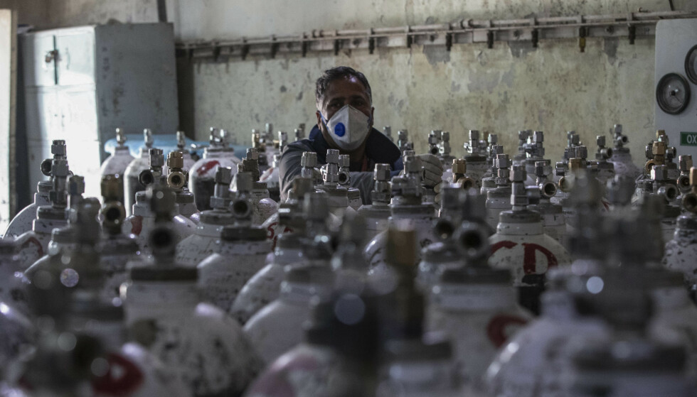 En sykehusansatt ser over oksygenflasker på et sykehus i Srinagar i India. Landet er hardt rammet av pandemien og oksygenmangelen er kritisk på en lang rekke sykehus. Foto: Mukhtar Khan / AP / NTB