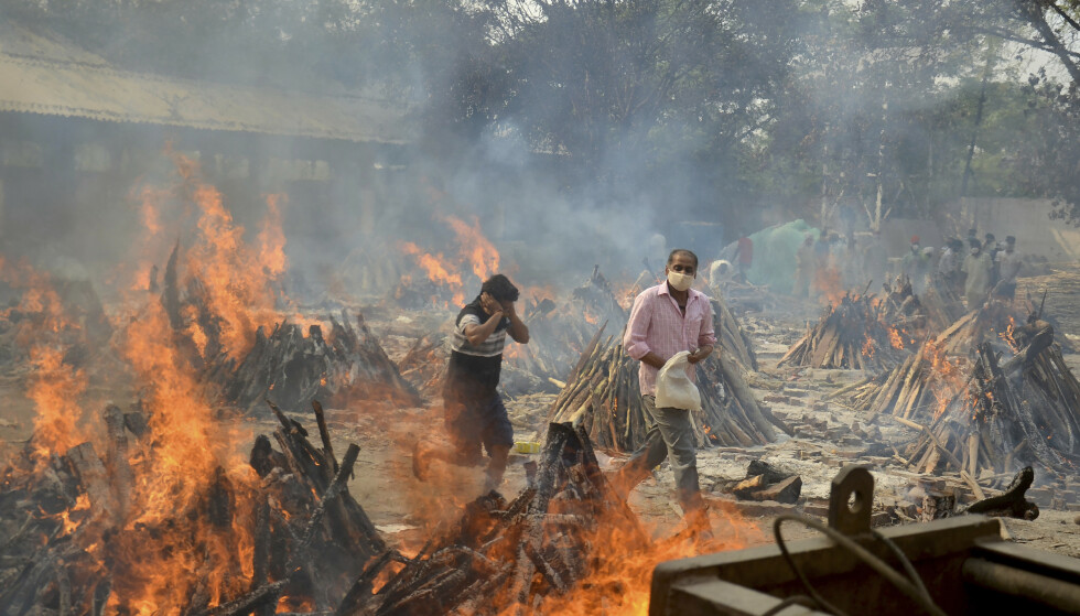 Relatives react to heat emitting from the multiple funeral pyres of COVID-19 victims at a crematorium in the outskirts of New Delhi, India, Thursday, April 29, 2021. (AP Photo/Amit Sharma)