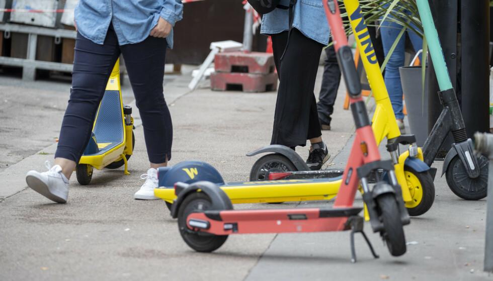 Elektriske sparkesykler står parkert på fortau og i veien et sted i Oslo. Den nye loven skal gi kommunene større mulighet til å avverge slike og andre farlige situasjoner. Foto: Terje Pedersen / NTB