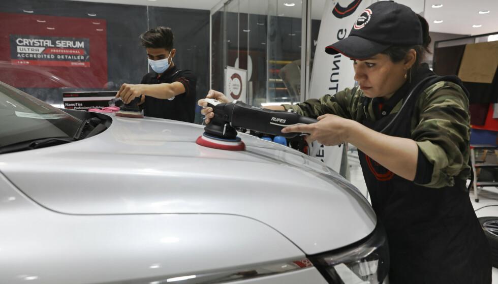 Det tradisjonelle hodetørkleet er byttet ut med caps når iranske Maryam Roohani er på jobb som bilpleier i det ellers sterkt mannsdominert yrke Foto: AP/Vahid Salemi-NTB