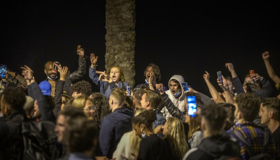 Folk er samlet for å feire på en strand i Barcelona. Ved midnatt søndag var en seks måneder lang periode med strenge coronarestriksjoner for hele landet forbi. Foto: Emilio Morenatti / AP / NTB