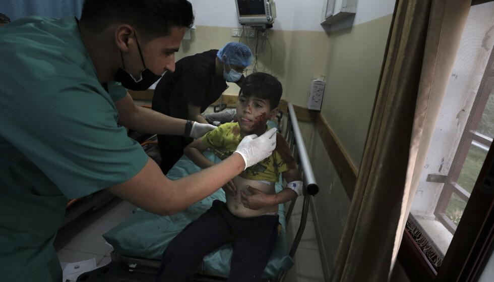 En palestinsk helsearbeider behandler en såret gutt i Beit Lahiya på Gazastripen mandag. Foto: AP/NTB