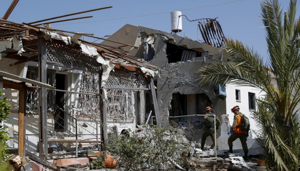 Israelske soldater gjennomsøker et hus i Ashkelon som ble truffet av en rakett fra Gazastripen tirsdag. Foto: AP/NTB