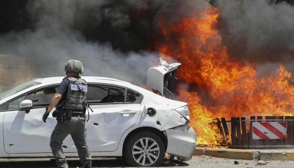 En bil brenner i den israelske byen Ashkelon etter å ha blitt truffet i et palestinsk rakettangrep tirsdag. Foto: AP/NTB