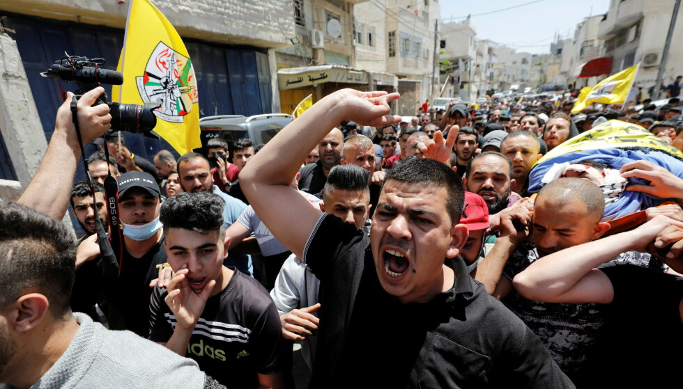 A mourner reacts as others carry the body of Palestinian man Hussien al-Titi, who was killed during stone-throwing clashes with Israeli forces, during his funeral at Fawwar refugee camp near Hebron, in the Israeli-occupied West Bank, May 12, 2021. REUTERS/Mussa Qawasma