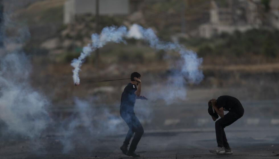 En palestiner kaster tilbake en tåregassgranat mot soldatene som avfyrte den under demonstrasjoner på Vestbredden mandag. Foto: Majdi Mohammed / AP / NTB