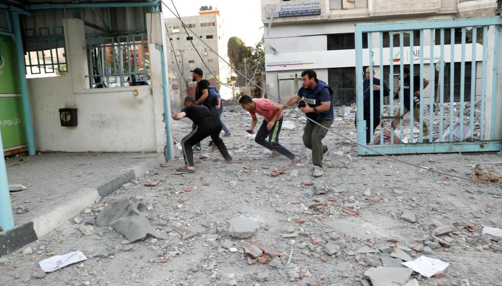 Journalister og andre løper i dekning under et israelsk flyangrep mot helsedepartementets bygning i Gaza by. Foto: AP / NTB