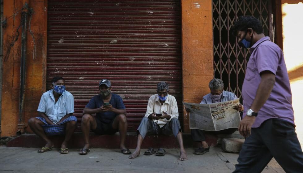 Folk iført munnbind utenfor en stengt butikk i Bangalore onsdag. Foto: Aijaz Rahi / AP / NTB