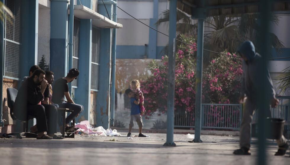 Palestinere på et tilfluktssenter som FN har opprettet på en skole på Gazastripen. 50 skoler har fått skader i israelske angrep i det palestinske området den siste uken, ifølge Redd Barna. Foto: Khalil Hamra / AP / NTB
