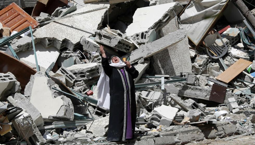 De israelske angrepene mot Gazastripen har forårsaket enorme ødeleggelser og kostet mange sivile livet, blant dem barn. Denne kvinnen står utenfor ruinene av bygningen som blant annet huset kontorene til nyhetsbyrået AP og TV-kanalen Al Jazeera. Foto: AP / NTB