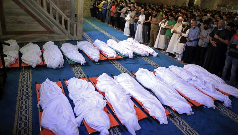 Sørgende ber for drepte palestinere på Gazastripen. Israels angrep har så langt kostet rundt 20 ganger så mange liv på palestinsk side, som det palestinske rakettangrep har kostet i Israel. Foto: AP / NTB