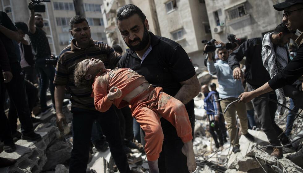 Over 2.100 palestinske barn er drept i israelske angrep de siste 20 årene. Her bæres et barn ut av ruinene av en boligblokk i Gaza by som ble bombet sist søndag. Foto: AP / NTB