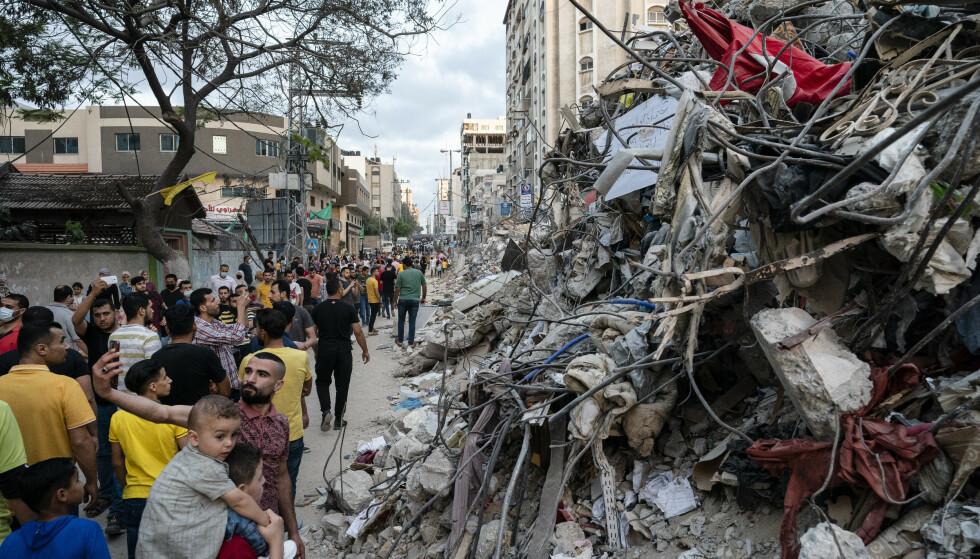 Etter at våpenhvilen trådte i kraft, er folk kommet ut for å se på bygninger som er lagt i grus av israelske flyangrep mot Gaza. Foto: John Minchillo / AP / NTB