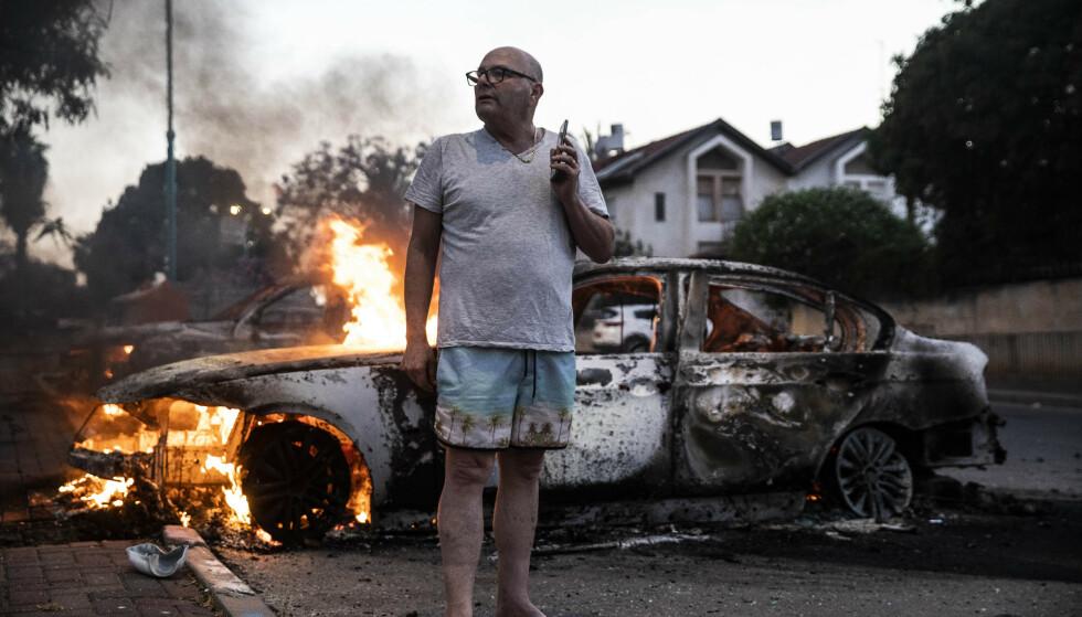 Jacob Simona står ved siden av sin brennende bil. Den ble satt fyr på under opptøyer mellom israelske arabere og jøder i byen Lod 11. mai. Foto: AP Photo