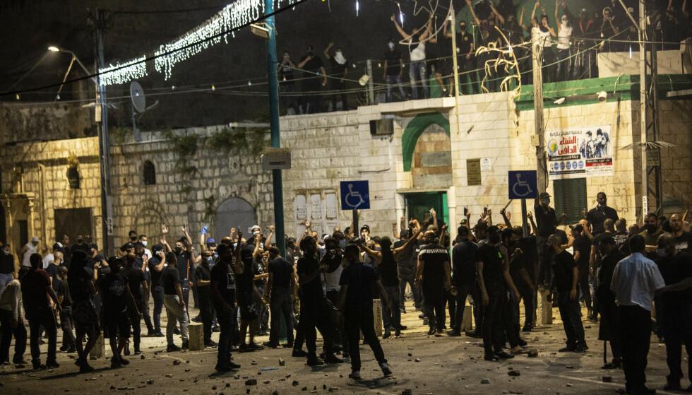 Israelske arabere samlet seg utenfor en synagoge under sammenstøt med israelske jøder i den israelske byen Lod. Det ble satt fyr på biler, en restaurant og en synagoge i den verste uroen i Israel på mange år. Foto: AP-NTB