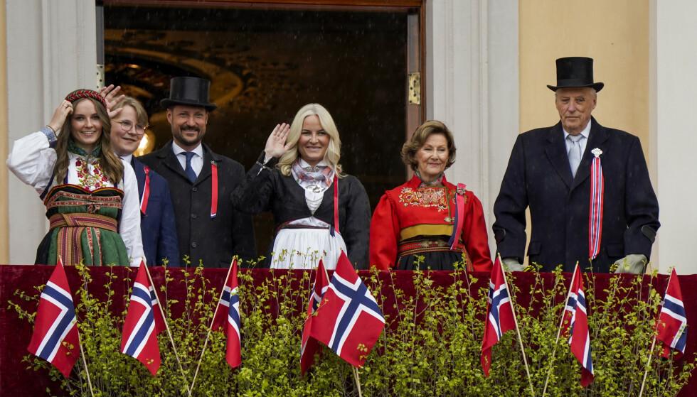 Kong Harald, dronning Sonja, kronprins Haakon, kronprinsesse Mette-Marit, prinsesse Ingrid Alexandra og prins Sverre Magnus hilser til folket fra balkongen på Slottet på 17. mai i år. Slottet har foreløpig ikke informert om hvem som skal få de ekstra dosene. Foto: Lise Åserud / NTB