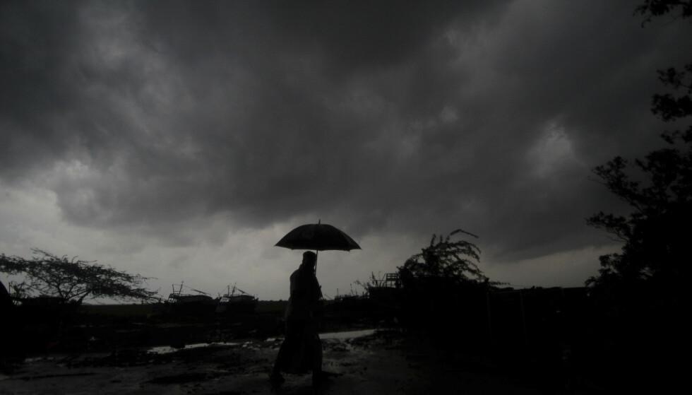 En landsbybeboer holder en paraply under mørke skyer i Balasore i Odisha tirsdag. Foto: AP / NTB