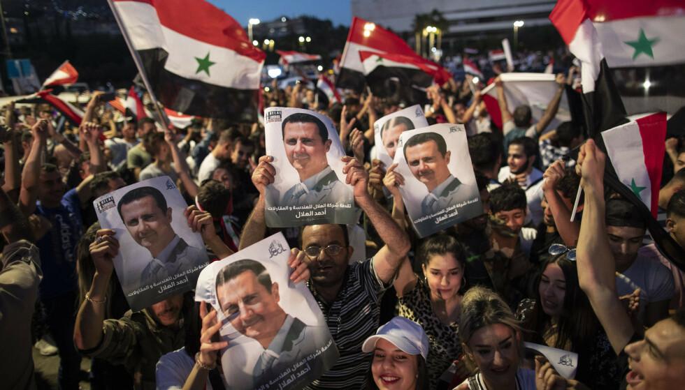 Jublende tilhengere av Syrias president Bashar Assad holder opp bilder av sin president etter valget. Foto: Hassan Ammar/AP/NTB