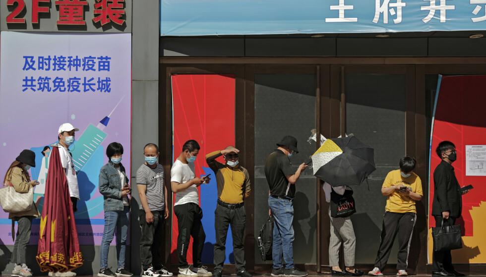 Kinesere i kø for å få coronavaksine i Beijing 17. mai. På en plakat ved vaksinasjonssenteret står følgende slagord: «Vaksinasjon til rett tid for sammen å bygge en kinesisk mur av immunitet». Foto: Andy Wong / AP / NTB