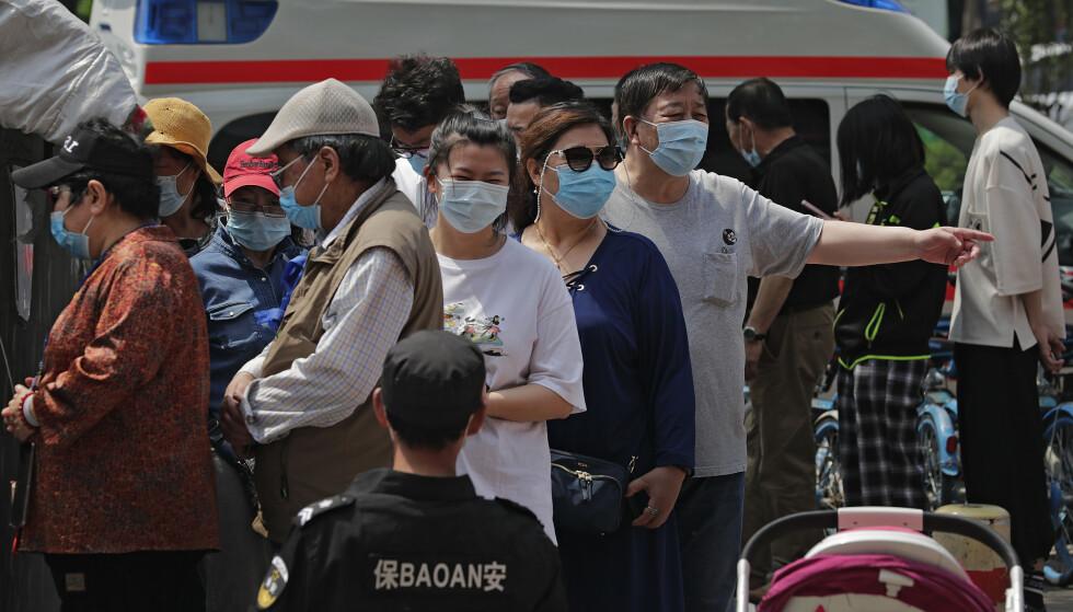 En sikkerhetsvakt fulgte med da folk sto i kø for å få coronavaksine ved en mobil vaksinestasjon i Beijing i midten av mai. Foto: Andy Wong / AP / NTB