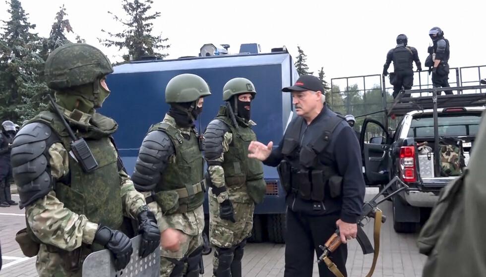 Hviterussland innfører strafferamme på opptil tre år for å delta i uautoriserte demonstrasjoner. Her er president Aleksandr Lukasjenko med sikkerhetsstyrker i forbindelse med demonstrasjoner mot regjeringen. Foto: Hviterussisk statlig fjernsyn via AP / NTB