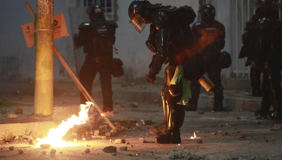 Opprørspoliti slukker en bensinbombe som ble kastet i deres retning under demonstrasjonene. Foto: Jairo Cassiani / AP / NTB