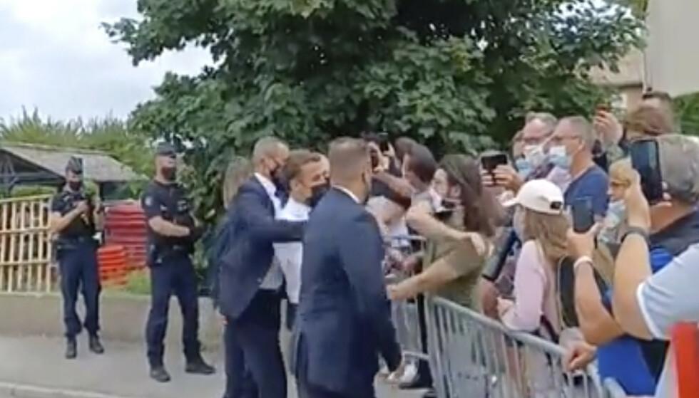 Mannen, i grønn t-skjorte, ga Macron, i hvit skjorte, en hard ørefik under et skolebesøk i Tain-l'Hermitage i Frankrike tidligere denne uken. Det ble han dømt til 18 måneders fengsel for. Foto: BFM TV/AP/NTB