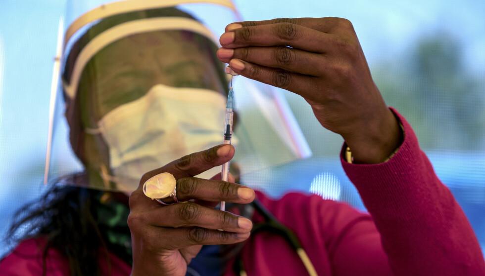 En helsearbeider forbereder en dose med Pfizer-vaksinen ved Orange Farm Clinic utenfor Johannesburg i Sør-Afrika. Svært få helsearbeidere i landet har selv fått vaksinen ennå. Foto: Themba Hadebe, AP / NTB