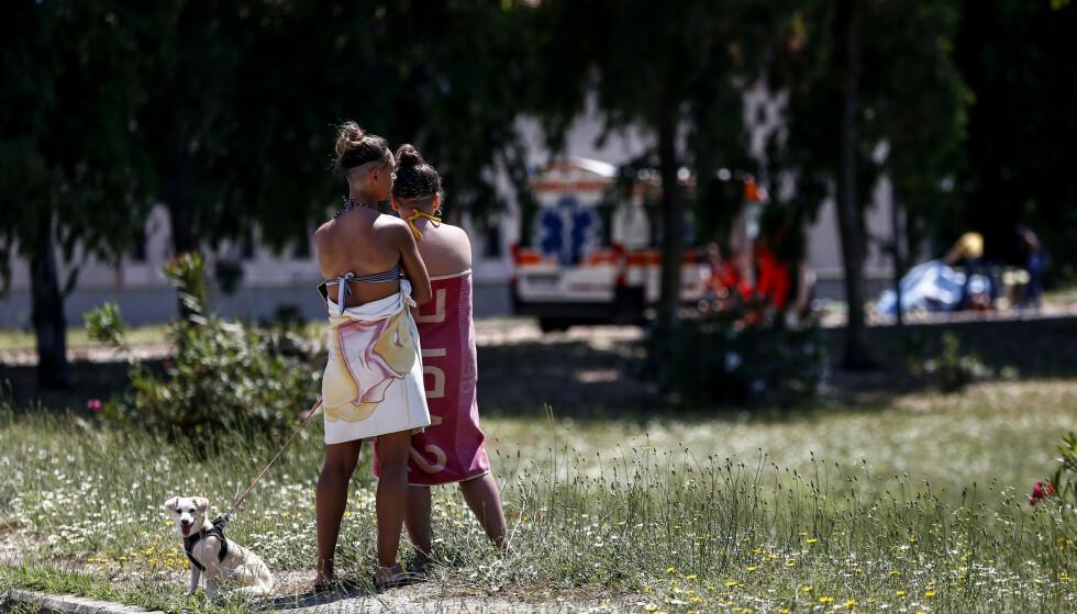 Sjokkerte strandgjengere iakttar parken der tre personer ble drept utenfor Roma. Foto: Cecilia Fabiano/LaPresse via AP/NTB