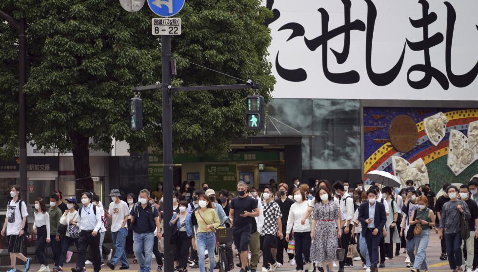 Fotgjengere med munnbind i Tokyo. Covid-19-pandemien herjer Japan og andre østasiatiske land i dag, men dette er ikke den første coronaepidemien i området. Ved å studere befolkningens gener har forskere funnet spor etter en lignende epidemi for 20.000 år siden. Foto: Eugene Hoshiko/AP/NTB