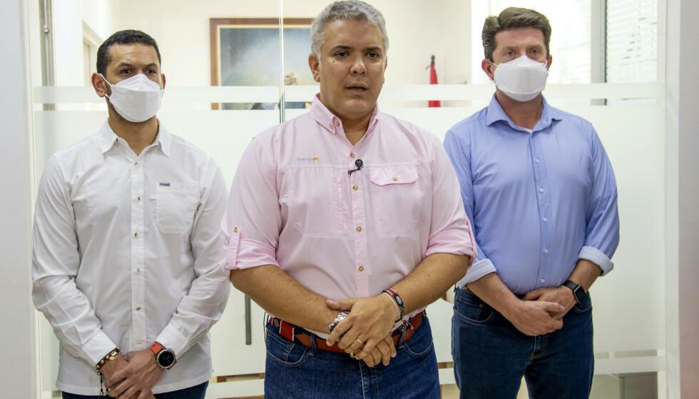 Ivan Duque, her flankert av innenriksminister Daniel Palacios (t.v.) og forsvarsminister Diego Molano, uttalte seg etter landing i Cúcuta. Foto: Cesar Carrion / Det colombianske presidentskapet via AP / NTB