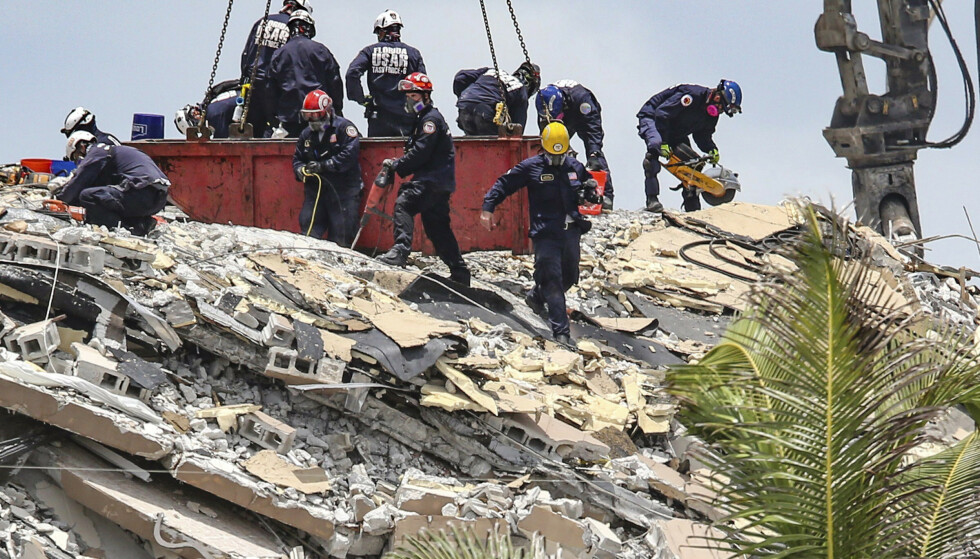 Redningsmannskaper leter i ruinene etter boligblokka i Surfside i Miami. Lørdag ble en femte person bekreftet omkommet. Foto: Al Diaz / Miami Herald via AP / NTB