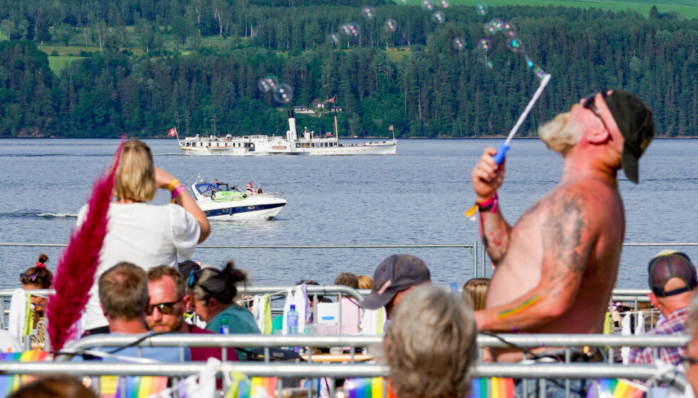 Mens Skibladner seiler forbi, hygger Odd Christian Hagen seg med å blåse såpebobler i finværet under Fredvikafestivalen på Gjøvik lørdag. Den lokale festivalen ved Mjøsa arrangeres denne helga for tredje gang etter oppstarten i 2018. 2020-utgaven ble i likhet med mange tilsvarende arrangementer avlyst, men i år er det comeback. Selv om det kun er gitt plass til et publikum på 600 er det tydelig at Festival-Norge så smått er i ferd med å våkne til live igjen. Foto: Heiko Junge / NTB