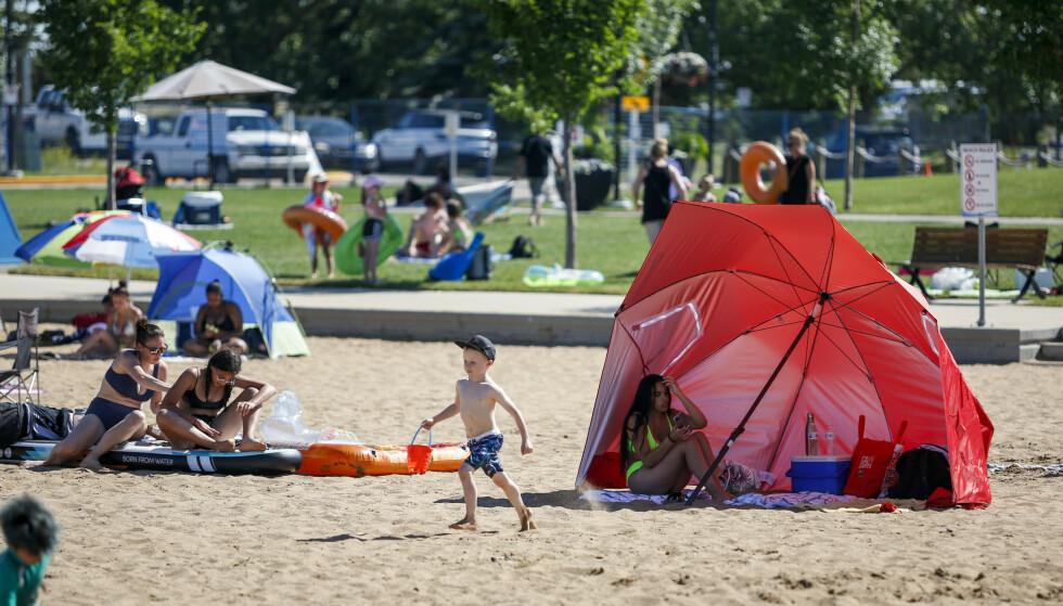 I Canada søker folk seg til stranden for å holde ut varmen. Her fra Chestermere. Foto: Jeff McIntosh / The Canadian Press via AP / NTB