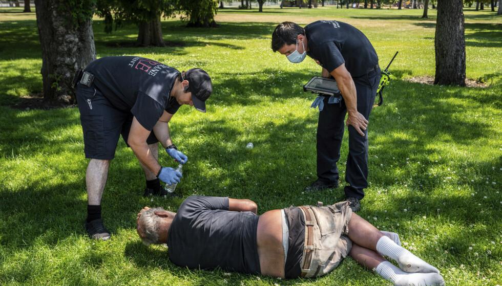 Her blir en mann sjekket i en park i Canada etter den ekstreme varmen. Foto: Colin Mulvany/The Spokesman-Review via AP via NTB