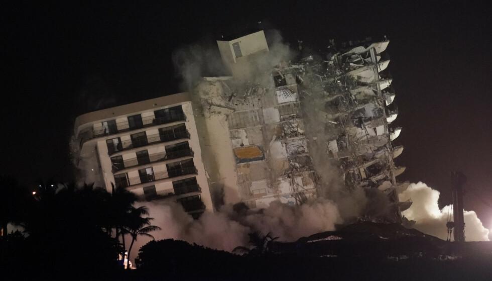 Det som var igjen av den kollapsede boligblokka i Surfside ved Miami Beach, ble revet natt til mandag lokal tid. Letingen var satt på pause i påvente av rivingen. 24 personer er funnet døde, mens 121 fortsatt ikke er gjort rede for. Foto: Lynne Sladky / AP / NTB