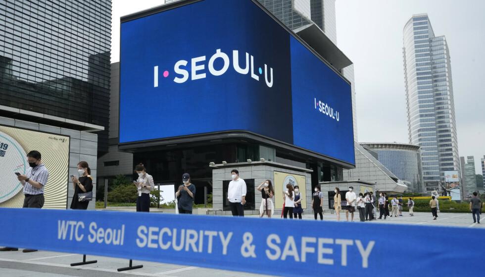 Folk i kø utenfor en teststasjon i Seoul. Den sørkoreanske regjeringen innfører de strengeste smitteverntiltakene til nå i hovedstadsområdet. Smittetallene er på sitt høyeste til nå i pandemien. Foto: Ahn Young-joon / AP / NTB
